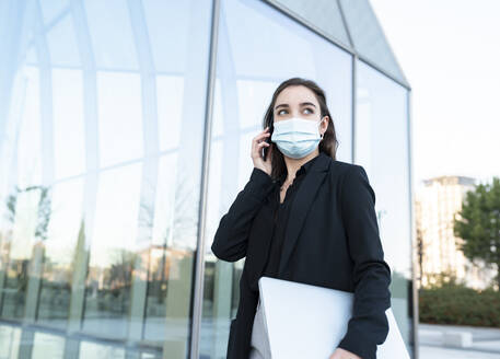 Businesswoman wearing face mask talking on mobile phone while standing against building - JCCMF00286