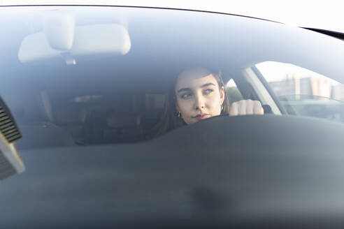 Young businesswoman looking away while sitting in car - JCCMF00295
