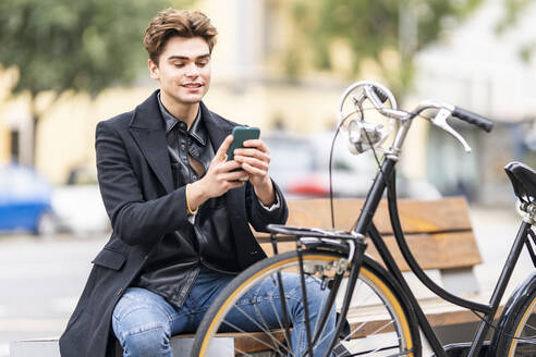 Young man text messaging through mobile phone while sitting on bench near bicycle in city - GGGF00535