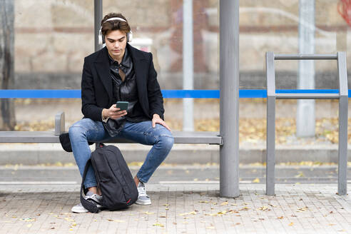 Handsome young man listening music while using smart phone sitting on bench at bus stop - GGGF00544