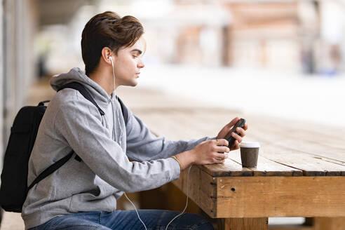 Handsome man listening music while using smart phone sitting at sidewalk cafe - GGGF00556