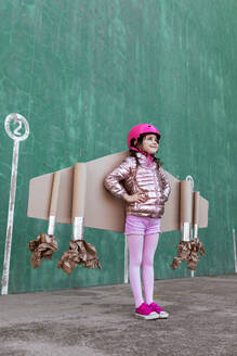 From below side view of cute girl in pilot helmet and handmade creative carton wings standing on street on green background looking away - ADSF19510