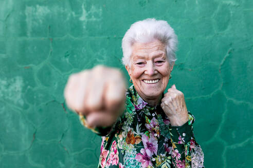 Cheerful elderly gray haired lady in stylish colorful blouse having fun and boxing at camera while standing against green wall - ADSF19522