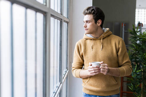 Young man with coffee cup contemplating while looking through window in new apartment - GIOF10271
