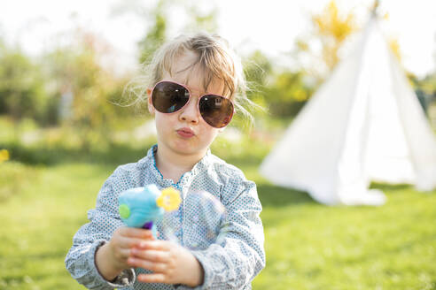 Girl wearing sunglasses playing with bubble gun while standing at garden - KVF00144