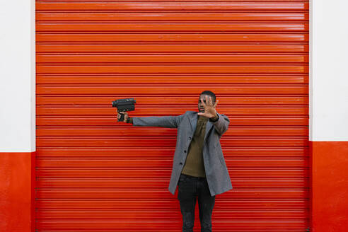 Man with old film camera showing stop gesture while standing against red wall - EGAF01321
