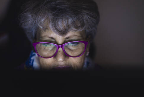 Close-up of teacher with gray hair working over laptop at home - OIPF00067