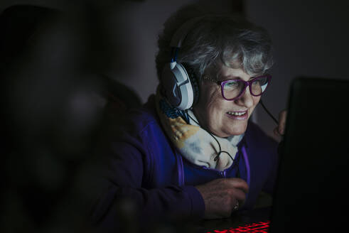 Close-up of smiling senior woman teaching over laptop at home - OIPF00070