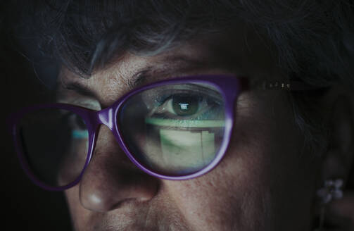 Close-up of senior woman wearing eyeglasses working at home - OIPF00073