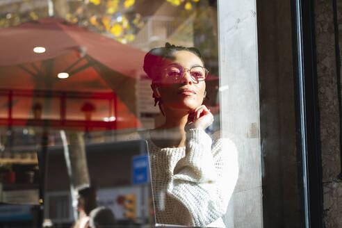 Confident young woman wearing eyeglasses looking through window at cafe - PNAF00409