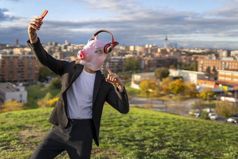 Businessman wearing pig mask and wireless headphones while taking selfie from smart phone on hill - GGGF00590