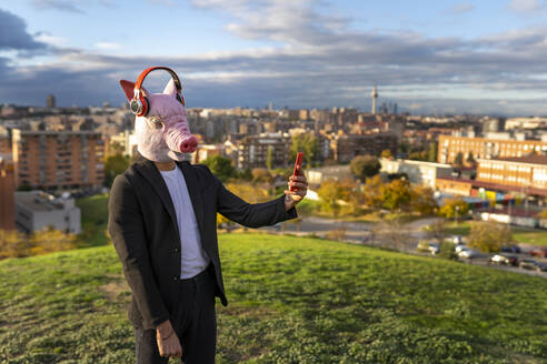 Businessman wearing pig mask and wireless headphones while taking selfie through smart phone on hill in city - GGGF00593