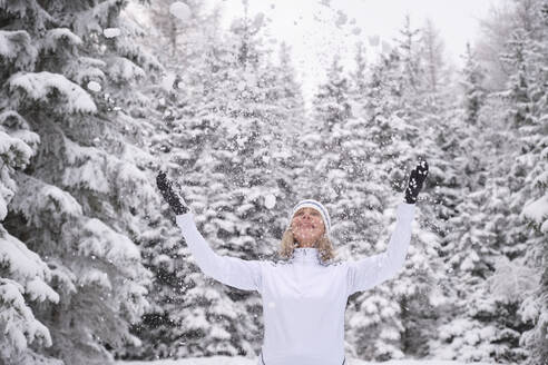 Happy senior woman enjoying snow against forest during vacations - MRF02425
