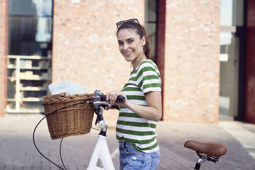 Cheerful woman with bicycle in city during weekend - ABIF01286