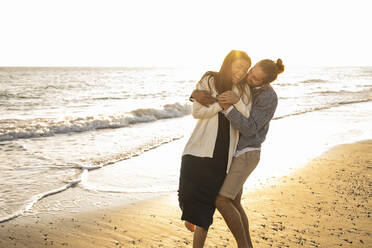 Cheerful couple enjoying at beach during sunny day - UUF22355
