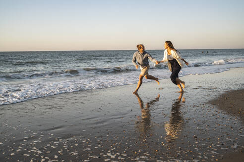Happy couple holding hands while running at beach against clear sky during sunset - UUF22358