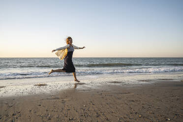 Cheerful young woman running at beach against clear sky during sunset - UUF22361
