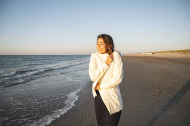 Happy young woman at beach against clear sky during sunset - UUF22364