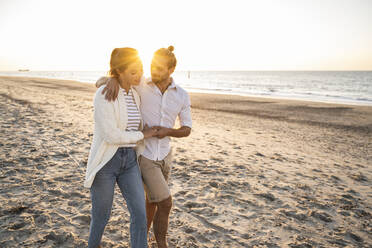 Young couple holding hands while walking at beach during sunny day - UUF22367