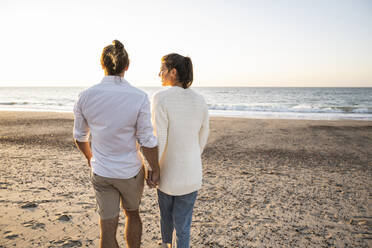 Young couple holding hands while walking at beach during sunset - UUF22370