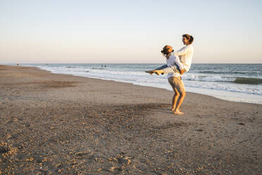 Carefree boyfriend lifting girlfriend at beach during sunset - UUF22376