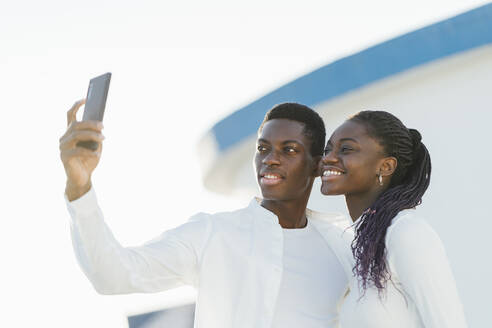 Smiling couple taking selfie through mobile phone against white wall - MPPF01374