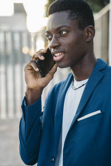 Young businessman in blazer talking on mobile phone call outdoors - MPPF01398