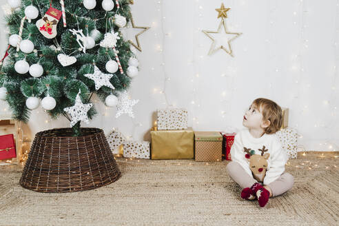 Baby girl looking at Christmas tree while sitting on carpet against wall - EBBF01953