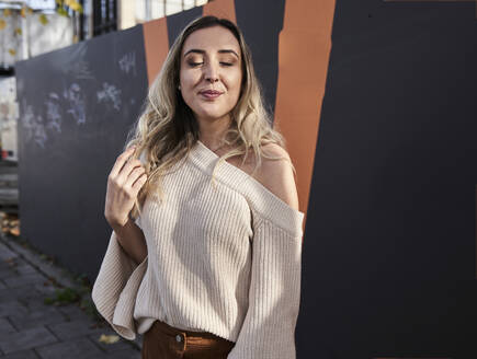 Beautiful woman with eyes closed standing against wall - SUF00656