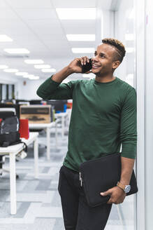 Smiling businessman holding file document while talking on phone call in corridor at office - JAQF00063