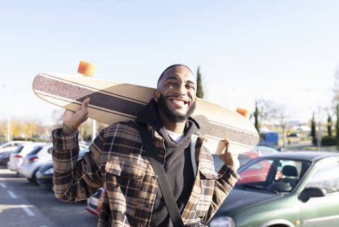 Happy young man carrying skateboard in parking lot against clear sky on sunny day - JCCMF00354