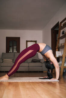 Young woman bending over backwards while exercising at home - GRCF00594