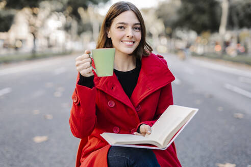 Smiling young woman with book having coffee while sitting on seat at street - JCZF00399