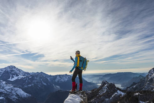 Mature male hiker using smart phone while standing on top of mountain, Orobic alps, Lecco, Italy - MCVF00703