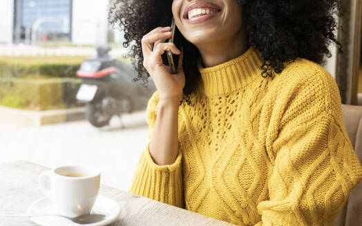Woman smiling while talking on mobile phone sitting at cafe - JCCMF00360