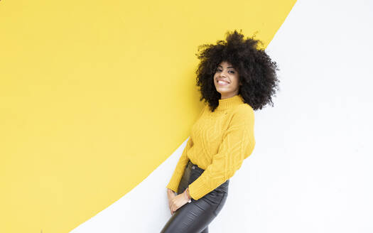 Young woman smiling while standing against colorful wall - JCCMF00375