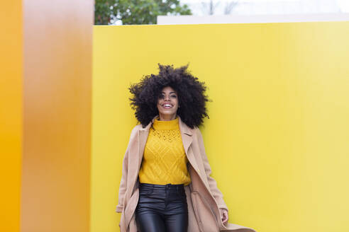 Young woman wearing jacket walking against yellow wall - JCCMF00411