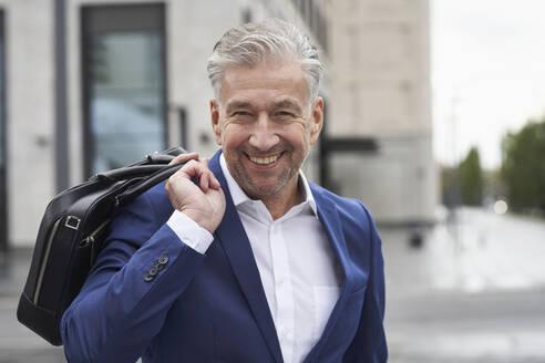 Smiling senior male entrepreneur holding laptop in city - SDAHF01081