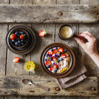 Female hand reaching for cup of coffee standing beside plate of quark with fruits and edible flowers - EVGF03851