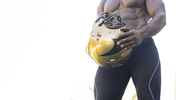 Male athlete holding sports helmet against clear sky on sunny day - JCCMF00440
