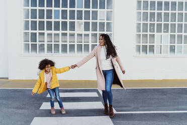 Cheerful mother and daughter holding hands while walking on road against building - EBBF01975