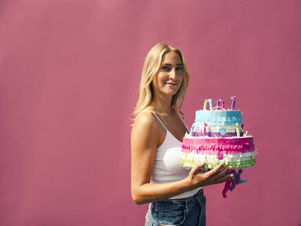Smiling woman with birthday cake against pink wall - GUSF04849