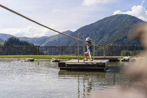 Little girl crossing lake on small wooden raft - DIGF13975