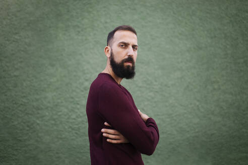 Bearded mid adult man with arms crossed standing by green wall - MIMFF00385