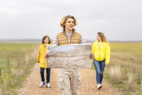 Three siblings hiking with map along dirt road - GGGF00632