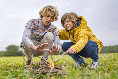 Two brothers starting campfire in grassy field - GGGF00647
