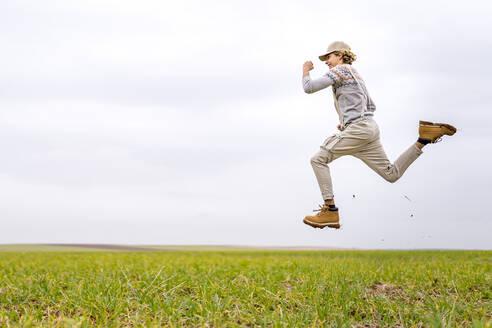 Young man jumping and posingmid-airin grassy field - GGGF00653