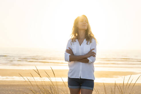 Mid adult woman standing wit arms crossed at beach during sunset - SBOF02328