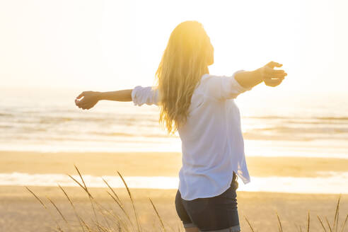 Woman standing with arms outstretched at beach during sunset - SBOF02331