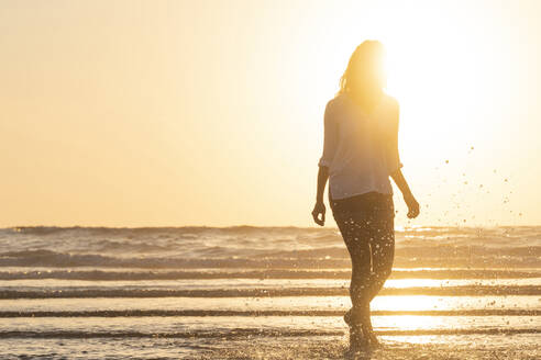 In silhouette of woman splashing water while standing at beach during sunset - SBOF02334